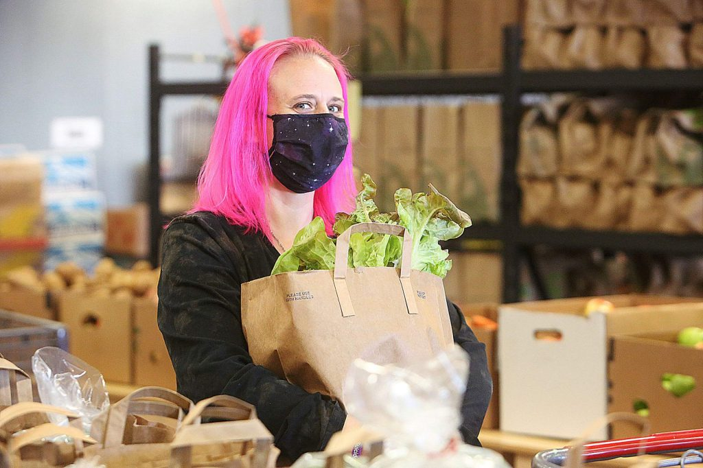 JoLynn Haines smiles from under her face mask as she stands with a bag of fresh produce from Interfaith Food Ministries.