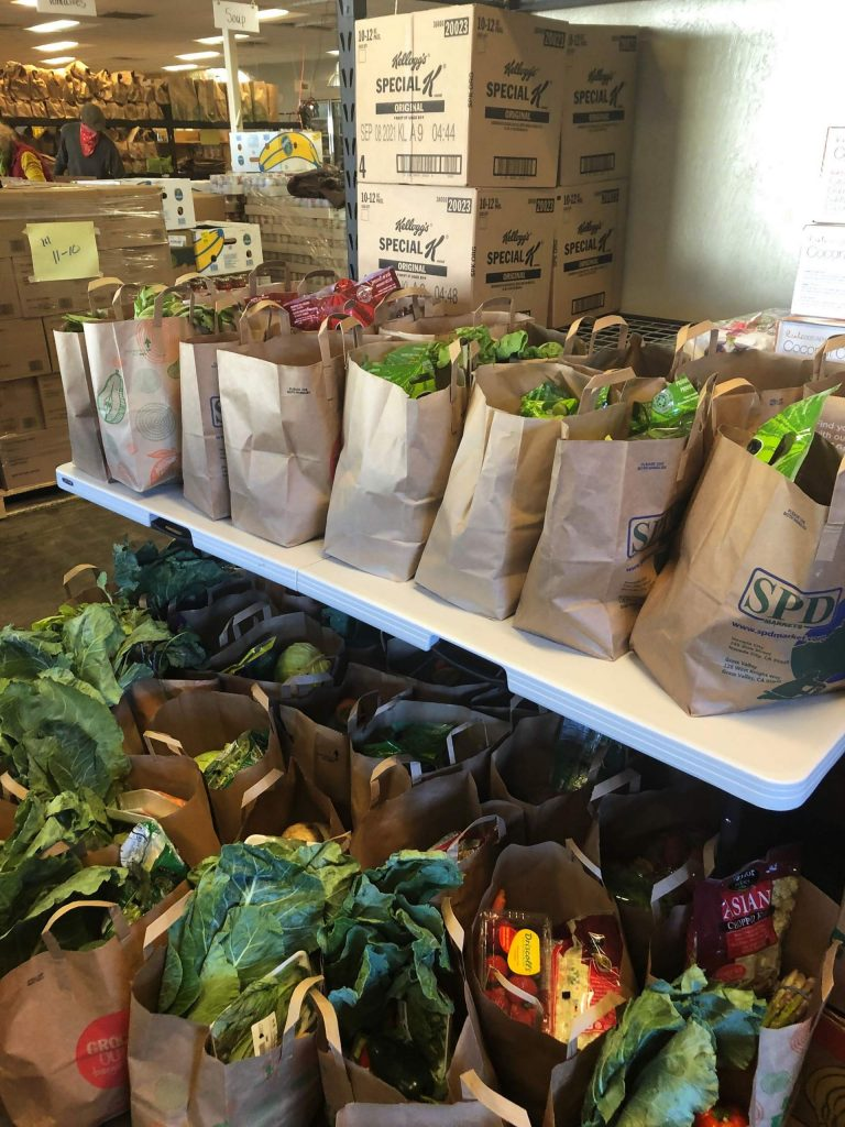 Rows of groceries with fresh produce are lined up at the Interfaith Food Ministry during a recent drive-thru food distribution day.