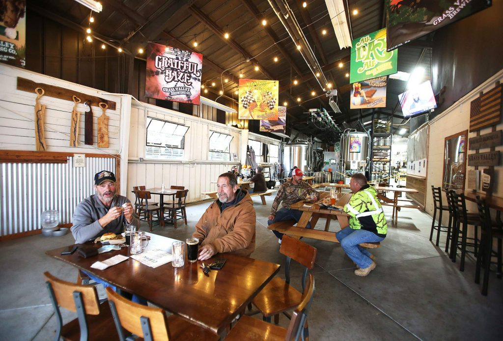 People enjoy a meal and a beer Wednesday at Grass Valley Brewing's newly remodeled warehouse dining space, which constitutes as outdoor dining due to the large rollup door.