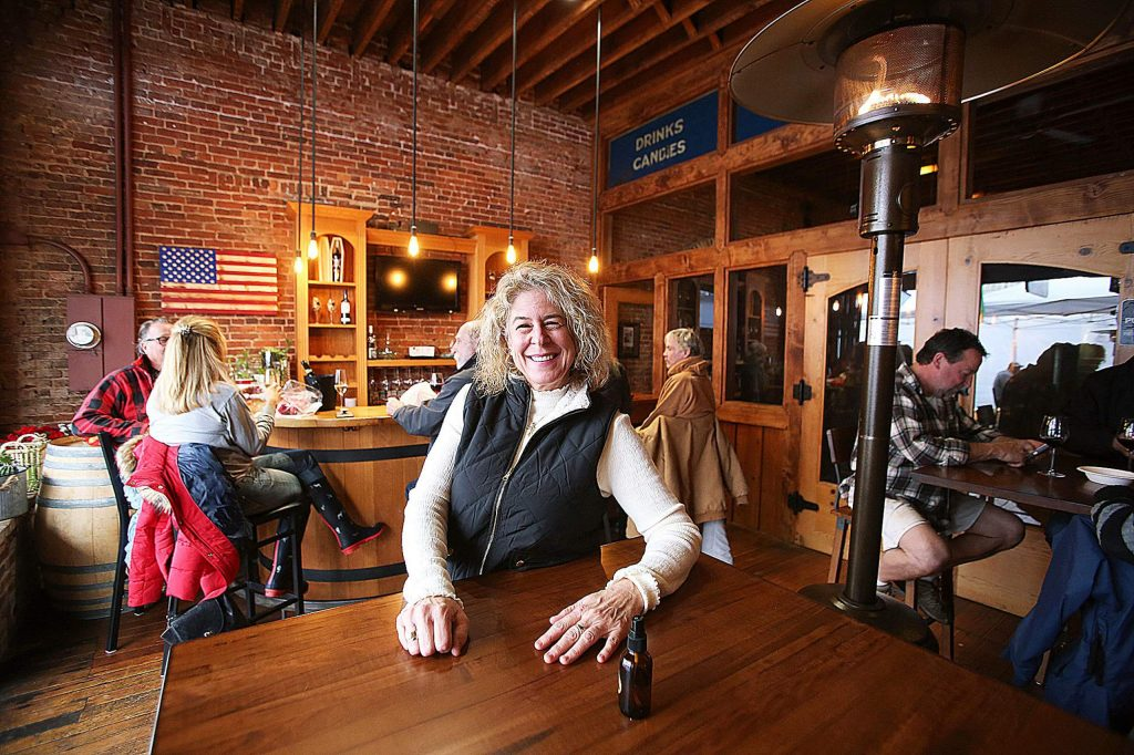 Cork 49's Anne Petronave smiles from her establishment's breezeway, which has been warmed with the help of an outdoor space heater. An outdoor tent has also been set up in front of their store and many others along Mill Street in downtown Grass Valley.