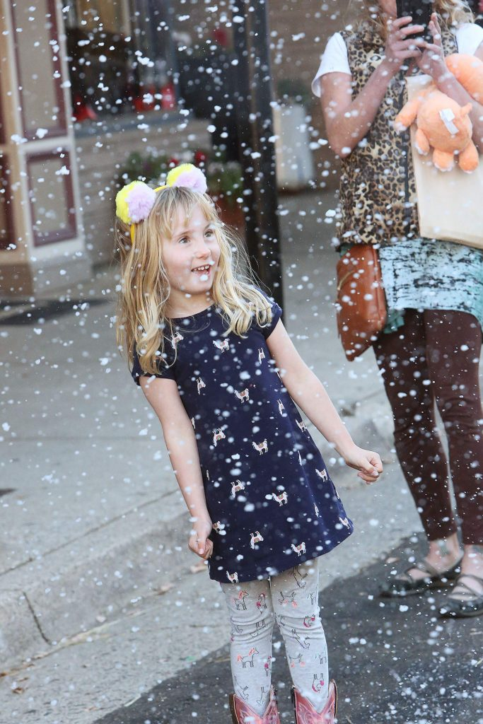 Five-year-old Harte Spiller takes a moment to admire the snowflakes falling in front of Stucki Jewelers in downtown Grass Valley Saturday.