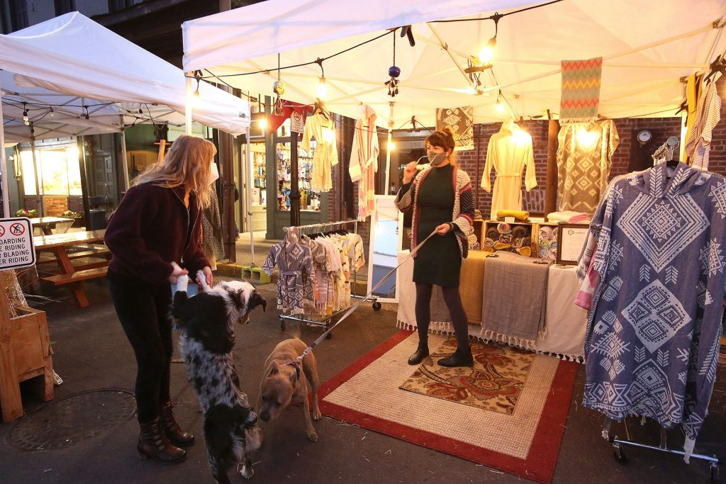 People check out the Tootkoo Turkish Cotton booth set up along Mill Street in downtown Grass Valley Fridays and Saturdays through the holiday shopping season.