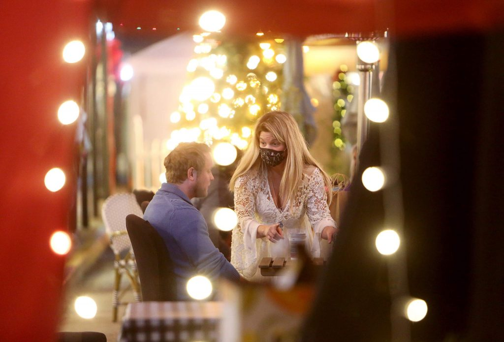 People are served along Mill Street's downtown street scene, lit up with twinkling Christmas lights for the holiday shopping and dining season.