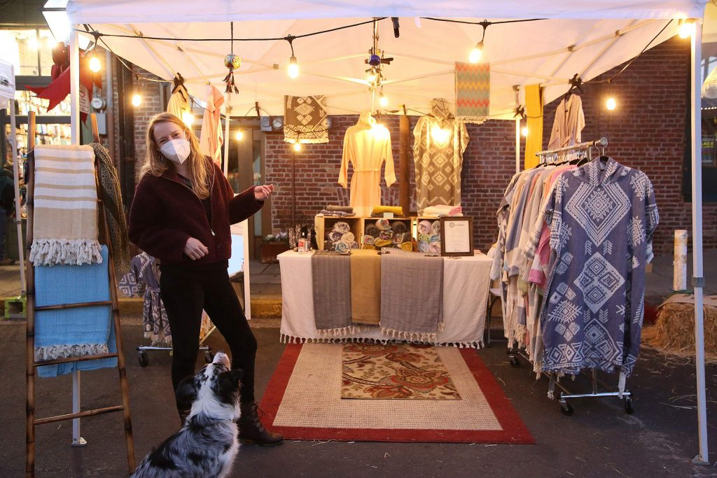 Annie Woodward and her dog Yara stand in front of the Tootkoo Turkish Cotton booth set up along Mill Street in downtown Grass Valley Fridays and Saturdays through the holiday shopping season.