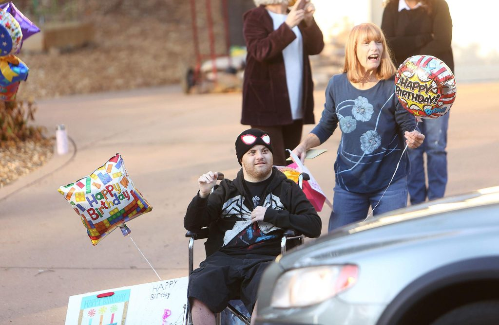 Skyler Monahan-Tonti and mother Bridget Monahan wave at the passing vehicles during Thursday's surprise birthday parade for Monahan-Tonti, who turned 33.