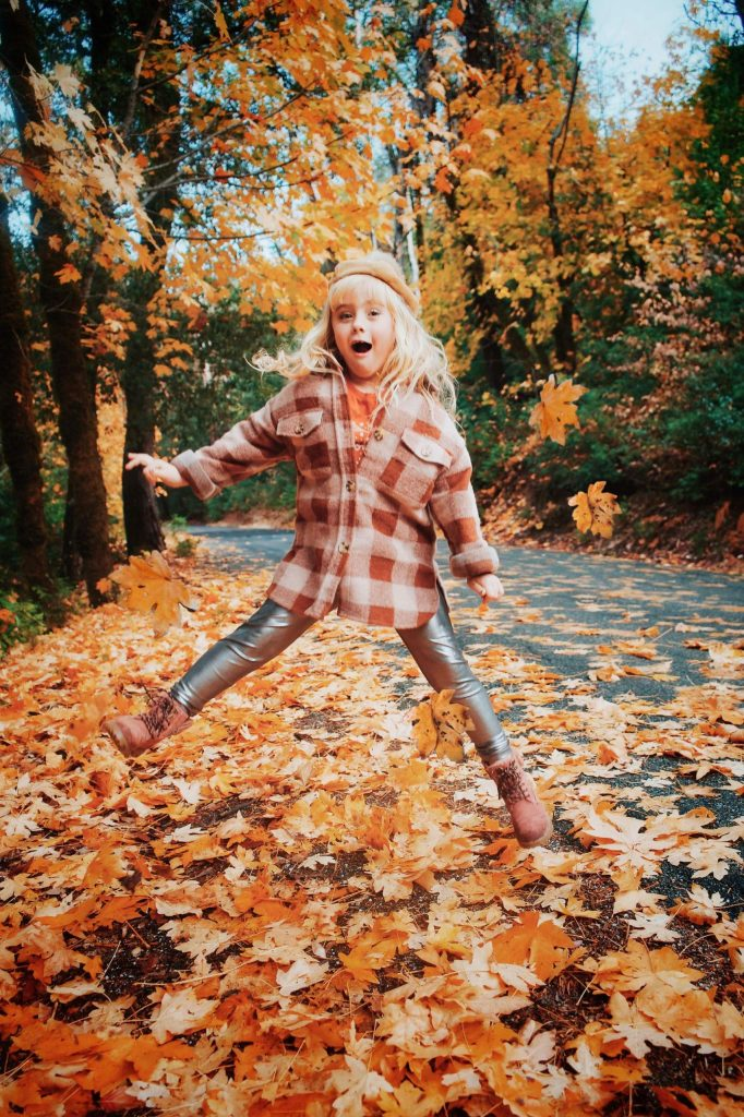 Holland Pedersen, 7, enjoys the fall leaves on Pasquale Road in Nevada City.