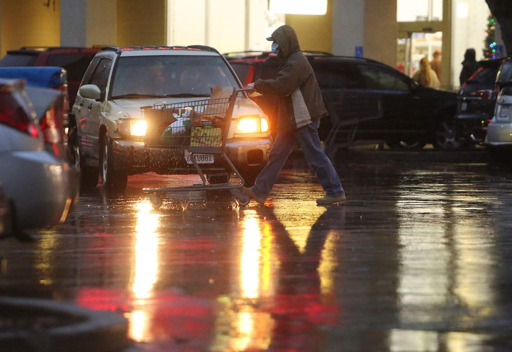 People push their carts full of goods to their vehicles despite Tuesday's rainfall.