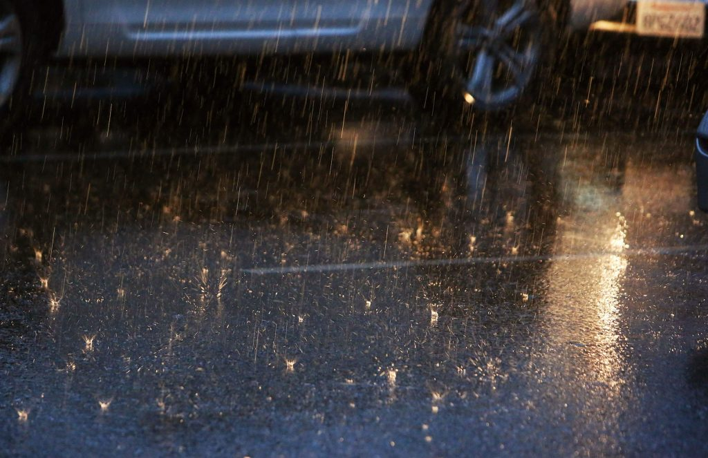 Heavy rain drops are illuminated by a vehicle's headlights as people get their shopping done in Grass Valley and Nevada City despite the rain.