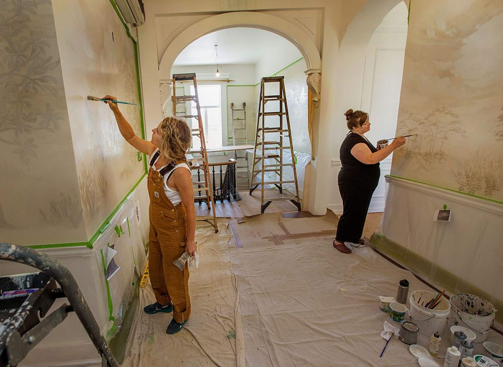 Sarah Coleman (left) and Brianna French painting a mural at the Holbrooke Hotel in June.