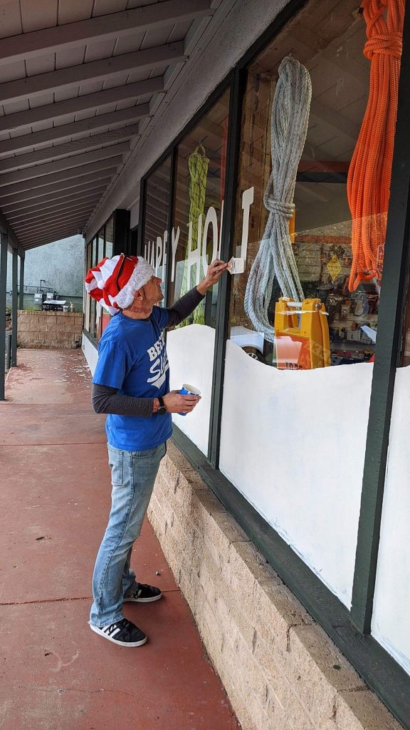 """David Haggard III letters """"Happy Holidays"""" onto Gold Country Tractor Supply's storefront windows last year."""